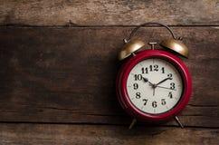 Rote Retro- Alarmglockeuhr auf alten Holzverkleidungen Stockbilder