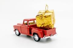 rote Retro- Autoaufnahme mit der gelben Geschenkbox lokalisiert Stockfotos
