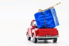 rote Retro- Autoaufnahme mit einer blauen Geschenkbox lokalisiert Lizenzfreies Stockfoto
