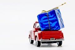 rote Retro- Autoaufnahme mit einer blauen Geschenkbox lokalisiert Lizenzfreies Stockbild