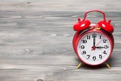 Rote Retro- Uhr, die 03:00 auf hölzernem Hintergrund zeigt Stockfotografie