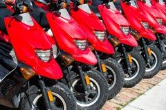 Rote Roller oder Motorräder für Verkauf oder Miete in der Reihe Stockfotografie
