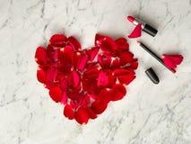 Rote rosafarbene Blumenblätter in der Herzform mit rotem Lippenstift auf Marmortischplattenhintergrund, Draufsicht St.-Valentinsg lizenzfreies stockfoto