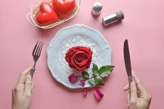 Rote Rose auf weißem Teller, mit Handholdinggabel und Messer und Paarherz im weißen Korb, auf rosa Hintergrund stockbilder
