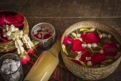 Rote Rose, Jasmin und geknallter Reis auf der ruhigen Wasseroberfläche, die auf das Holz tischfertig ist für gesetzt wird, gießt  stockfoto