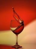 Rote Rose Wine Tempting Abstract Splashing auf Steigungshintergrund der Weiß-, Gelben und Rotenfarben auf dem reflektierenden Lizenzfreies Stockbild