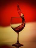 Rote Rose Wine Tempting Abstract Splashing auf Steigungshintergrund der Weiß-, Gelben und Rotenfarben auf dem reflektierenden Lizenzfreie Stockfotos