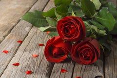 Rote Rosen auf altem Holztisch mit Konfettiherzen, Valentinsgruß ` s Tag Stockfotografie