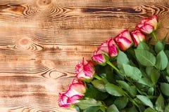 Rote Rosen auf h?lzernem Hintergrund stockbild