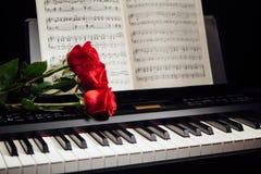 Rote Rosen auf Klavierschlüsseln und Musikbuch Stockfotos