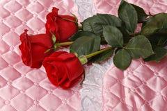 Rote Rosen auf rosa Satin Stockbild
