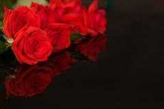 Rote Rosen auf Schwarzem stockbild