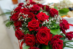 Rote Rosen der Dekoration der frischen Blumen an der Hochzeitstafelnahaufnahme Lizenzfreie Stockfotos