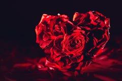 Rote Rosen in der Herzform auf Seidenhintergrund lizenzfreies stockfoto