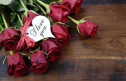 Rote Rosen des Valentinstags auf Dunkelheit bereiteten hölzernen Hintergrund auf Stockbild