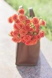 Rote Rosen in einer Tasche Stockbild