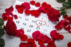 Rote Rosen gelegt auf den Kalender Stockbilder