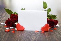 Rote Rosen, Herzen und Karte auf einem dunklen hölzernen Hintergrund Lizenzfreies Stockbild