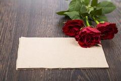 Rote Rosen, Herzen und Karte auf einem dunklen hölzernen Hintergrund Stockbilder