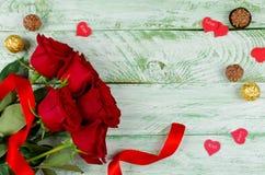 Rote Rosen, Herzen und Süßigkeit auf hölzernem Hintergrund Stockbild