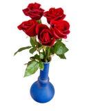 Rote Rosen im blauen Vase Stockbild