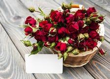 Rote Rosen im Korb und in der Grußkarte Lizenzfreies Stockbild