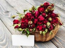 Rote Rosen im Korb und in der Grußkarte Lizenzfreies Stockfoto