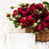 Rote Rosen im Korb und in der Grußkarte Stockfoto