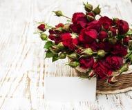 Rote Rosen im Korb und in der Grußkarte Stockfotos