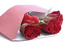 Rote Rosen im Umschlag auf Weiß Lizenzfreies Stockfoto