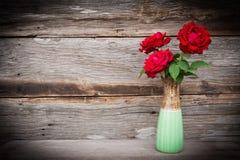 Rote Rosen im Vase auf hölzernem Hintergrund Stockfotos