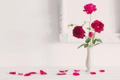 Rote Rosen im Vase auf Hintergrundweißwand Stockfotografie
