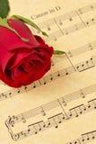 Rote Rosen-Knospe auf Blatt-Musik Lizenzfreie Stockfotos