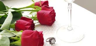 Rote Rosen legen auf weiße Tabelle nahe silbernem Ring mit großem klarem Diamanten stockbilder
