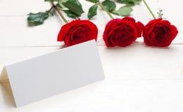 Rote Rosen mit einer unbelegten Anmerkung Lizenzfreies Stockfoto
