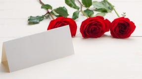 Rote Rosen mit einer unbelegten Anmerkung Stockfoto