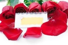Rote Rosen mit einer unbelegten Geschenkkarte Lizenzfreie Stockbilder