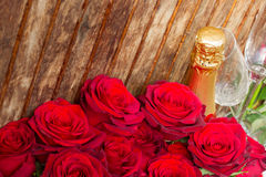 Rote Rosen mit Hals des Champagners Stockfoto