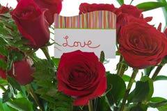Rote Rosen mit Karte, die sagt   Lizenzfreie Stockfotos