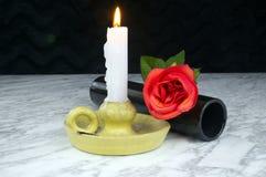 Rote Rosen mit schwarzem Vase, Kerze auf der Marmortabelle Lizenzfreie Stockfotografie