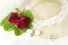 Rote Rosen und Eheringe Stockbild