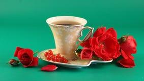 Rote Rosen und eine Tasse Tee Lizenzfreies Stockfoto