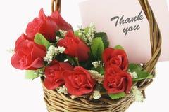 Rote Rosen und Gruß-Karte im Korb Lizenzfreies Stockfoto