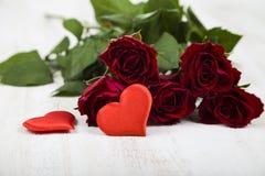 Rote Rosen und Herzen auf einem hölzernen Hintergrund Lizenzfreie Stockfotos