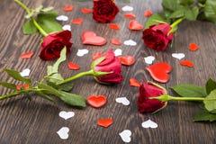 Rote Rosen und Herzen auf einem hölzernen Hintergrund Stockfotos