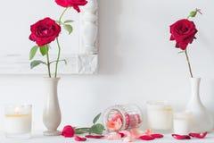 Rote Rosen und Kerzen auf weißem Hintergrund Stockbild