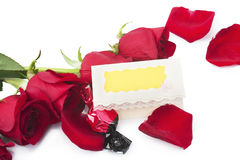 Rote Rosen und Süßigkeit mit einem leeren Gutschein Stockfoto