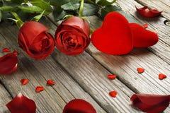 Rote Rosen und Samtherzen auf altem Holztisch, Valentinsgruß ` s Tag Lizenzfreie Stockfotos