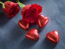 Rote Rosen und Schokoladenherzen auf einem dunkelblauen Hintergrund Stockfotos
