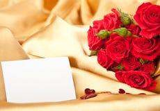 Rote Rosen und unbelegte Karte auf goldenem Satin lizenzfreie stockfotos